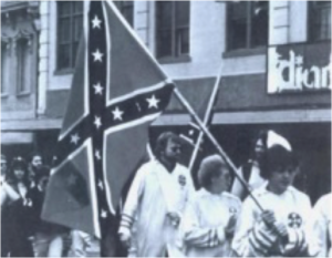 KKK members marching against desegregation carrying the Confederate battle flag